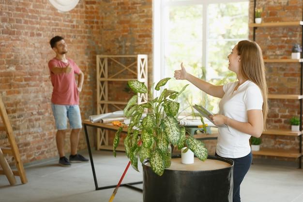 一緒にアパートの修理をしている若いカップル。家のイメージチェンジやリフォームをしている既婚男性と女性。関係、家族、愛の概念。完成したデザインをチェックし、新しい家具を置きます。