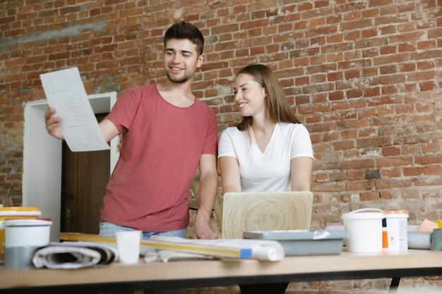 一緒にアパートの修理をしている若いカップル。家のイメージチェンジやリフォームをしている既婚男性と女性。関係、家族、愛の概念。ノートブックを使用して壁のデザインについて話し合います。
