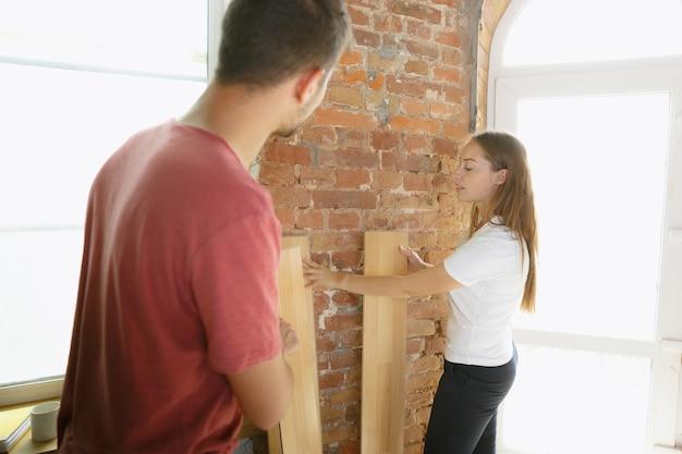 一緒にアパートの修理をしている若いカップル。家のイメージチェンジやリフォームをしている既婚男性と女性。関係、家族、愛の概念。ラミネートフローリングを敷き詰めて、笑顔で、幸せそうに見えます。