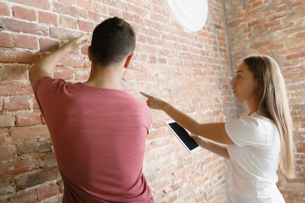 一緒にアパートの修理をしている若いカップル。家のイメージチェンジやリフォームをしている既婚男性と女性。関係、家族、愛の概念。壁の将来の設計を測定して話し合います。