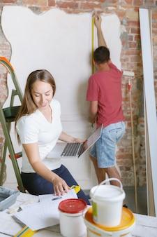 一緒にアパートの修理をしている若いカップル。家のイメージチェンジやリフォームをしている既婚男性と女性。関係、家族、愛の概念。塗装前の壁の測定、デザイン作成。