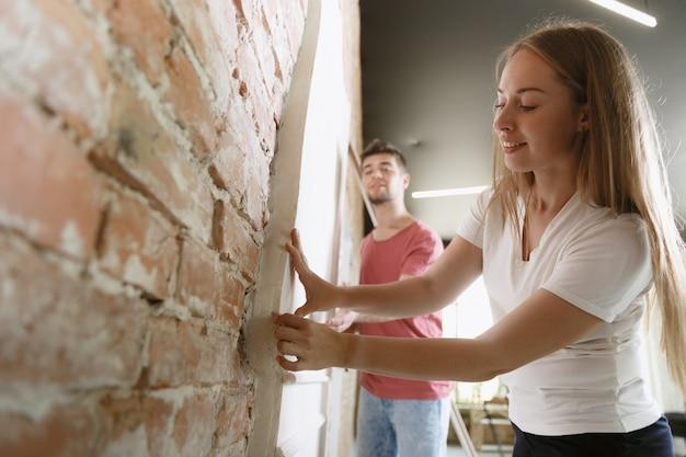 Молодая пара вместе делает ремонт квартиры. женатые мужчина и женщина делают домашний ремонт или ремонт. понятие отношений, семьи, любви. обмер стены, подготовка к дизайну.