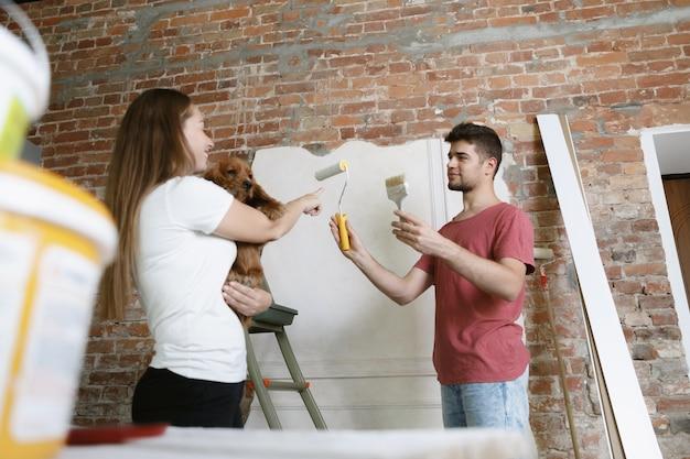 一緒にアパートの修理をしている若いカップル。家のイメージチェンジやリフォームをしている既婚男性と女性。関係、家族、ペット、愛の概念。犬を抱きかかえて壁を塗る。