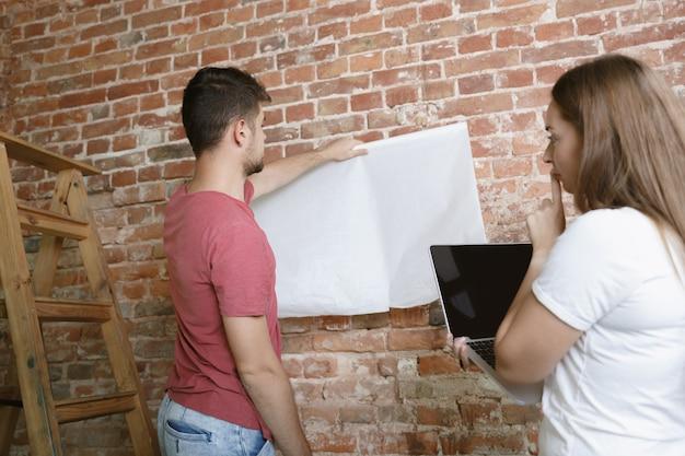 一緒にアパートの修理をしている若いカップル。家のイメージチェンジやリフォームをしている既婚男性と女性
