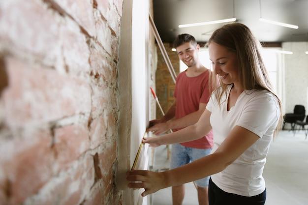 Молодая пара вместе делает ремонт квартиры. женатые мужчина и женщина делают домашний ремонт или ремонт