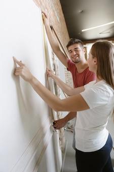 Giovani coppie che fanno insieme la riparazione dell'appartamento. uomo e donna sposati che fanno rifacimento o ristrutturazione della casa. concetto di relazioni, famiglia, amore. misurare il muro, prepararsi per il design.