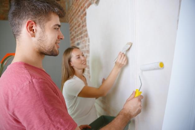 Giovani coppie che fanno insieme la riparazione dell'appartamento. uomo e donna sposati che fanno rifacimento o ristrutturazione della casa. concetto di relazioni, famiglia, amore. dipingere il muro insieme e ridere.