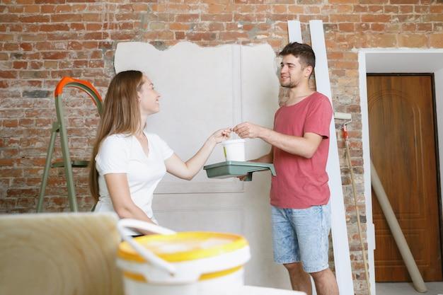 Giovani coppie che fanno insieme riparazione dell'appartamento. uomo e donna sposati che fanno rifacimento o ristrutturazione della casa. concetto di relazioni, famiglia, amore. dipingere il muro insieme e ridere.