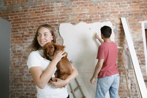 Giovani coppie che fanno insieme riparazione dell'appartamento. uomo e donna sposati che fanno rifacimento o ristrutturazione della casa