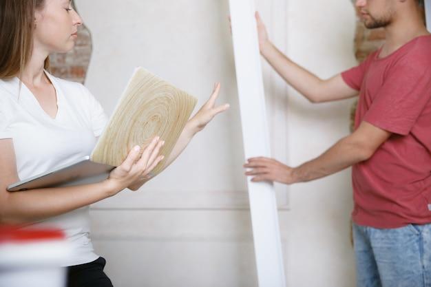 Giovani coppie che fanno insieme riparazione dell'appartamento.