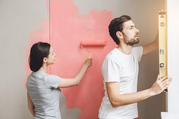 一緒にアパートの修理をしている若いカップル