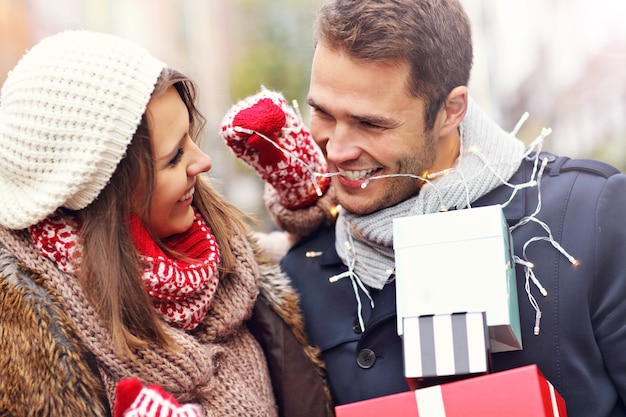 街でクリスマスの買い物をしている若いカップル
