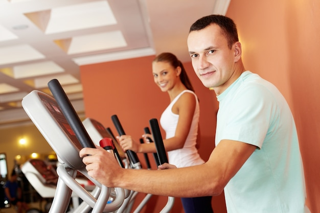 Young couple doing exercises with elliptical trainer