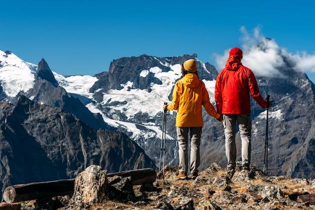 산, 후면 보기에서 노르딕 워킹을 하는 젊은 부부. 활동적인 커플이 하이킹에 종사하고 있습니다. 젊은 부부가 추적에 종사하고 있습니다. 트레킹과 노르딕 워킹. 등산. 복사 공간