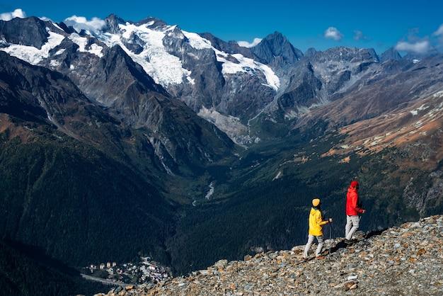 산, 후면 보기에서 노르딕 워킹을 하는 젊은 부부. 활동적인 커플이 하이킹에 종사하고 있습니다. 젊은 부부가 추적에 종사하고 있습니다. 트레킹과 노르딕 워킹. 등산. 돔베이. 복사 공간