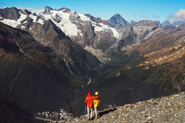 Young couple doing nordic walking in the mountains, rear view. an active couple is engaged in hiking. a young couple is engaged in tracking. trekking and nordic walking. hiking. copy space
