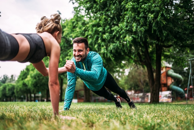 Young couple doing one hand push-up exercise in the park.