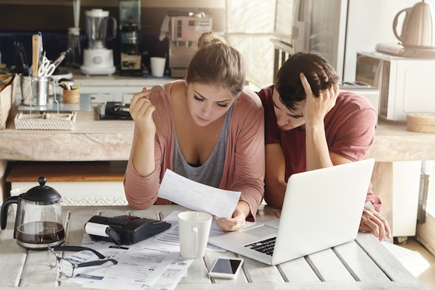 キッチンで書類をやっている若いカップル:欲求不満の女性がラップトップでテーブルに座って、必死で頭を抱えている夫と一緒に文書を読んで