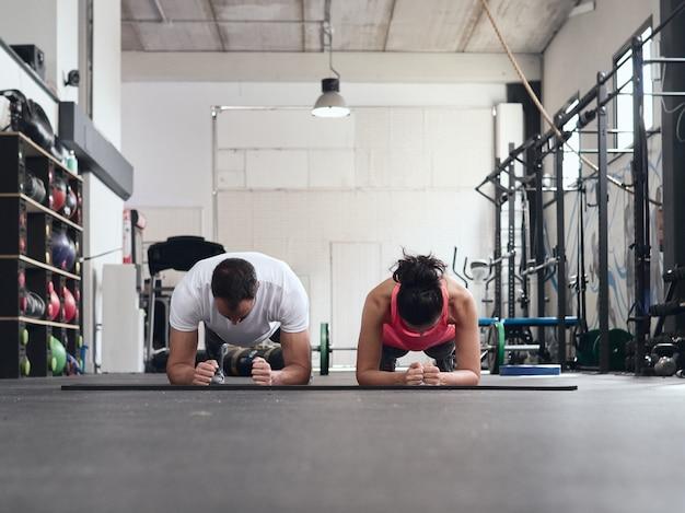Молодая пара делает доски в тренажерном зале пустого кроссфита