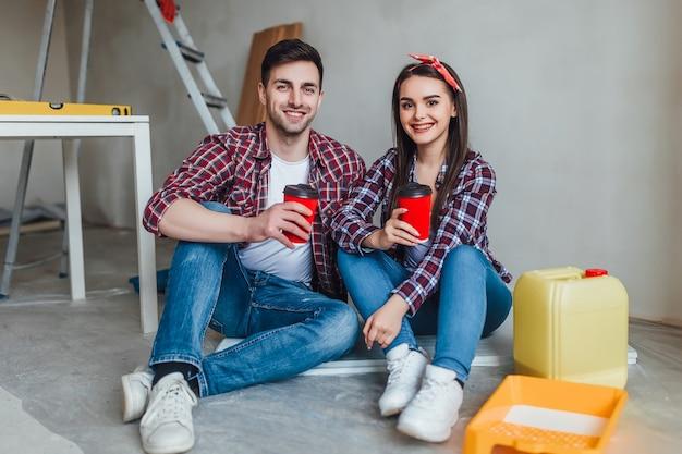 修理をしている若いカップルは、おいしいコーヒーのカップで休憩時間を過ごします