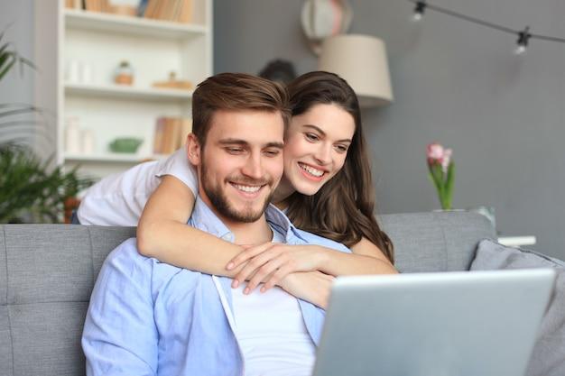 ソファの上のラップトップを使用して、自宅でいくつかのオンラインショッピングをしている若いカップル。
