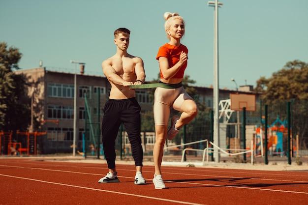 Молодая пара занимается спортом со спортивными резинками