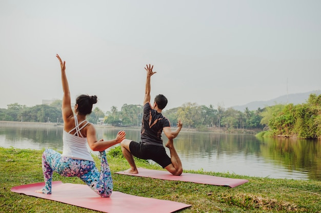 Young couple doing yoga next to the lake