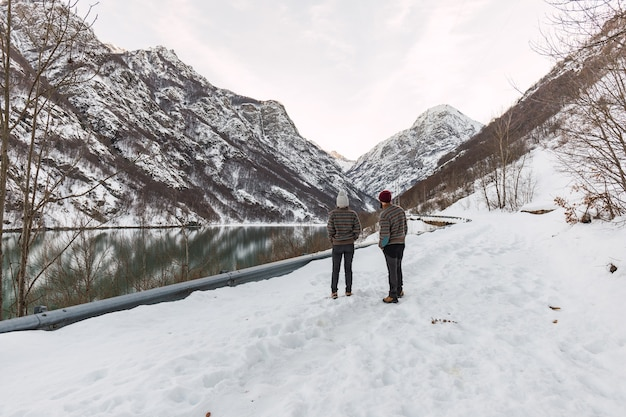 Young couple dressed alike in winter clothes on snowy mountain beside a frozen lake.