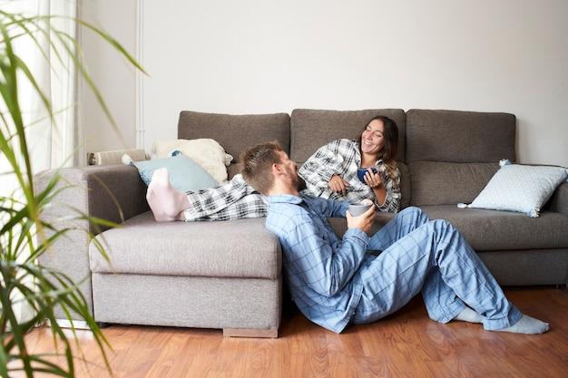 Молодая пара, одетая в пижаму дома. они счастливы и смеются на празднике, наслаждаясь вместе.