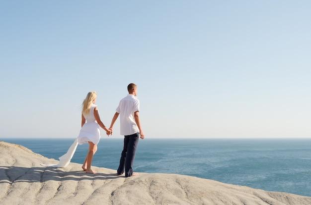 Молодая пара, одетая в белое, держась за руки и глядя на море