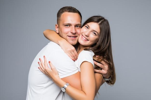 孤立したロマンチックなフレンドリーな抱擁を持っている白いtシャツに身を包んだ若いカップル