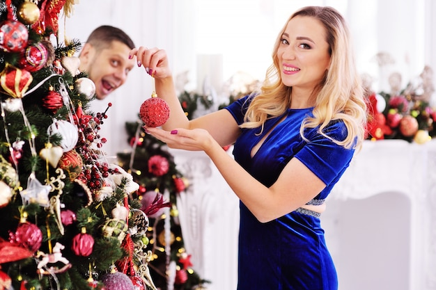 A young couple dresses up a christmas tree-a woman hangs toys on the tree