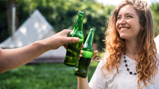 Young couple drinking beer, smiling, clinking bottles. greenery around. glamping
