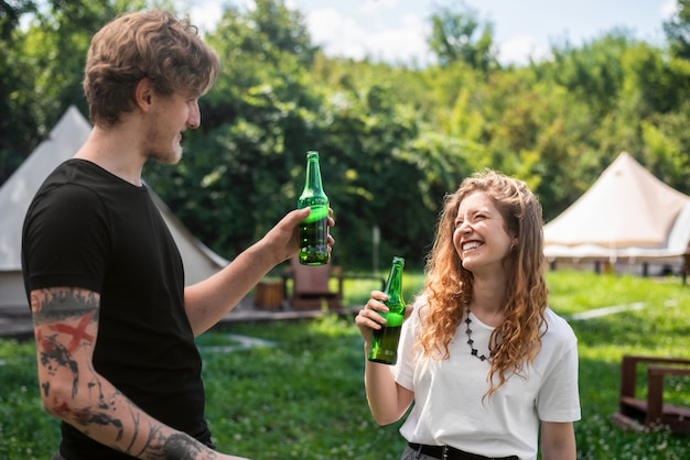 Young couple drinking beer, smiling. greenery around. glamping