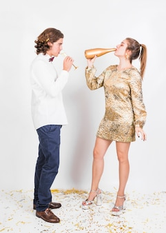 Young couple drinking champagne from glass and bottle