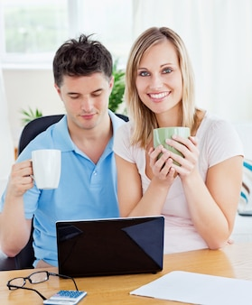 Молодая пара пить кофе и работать вместе на ноутбуке