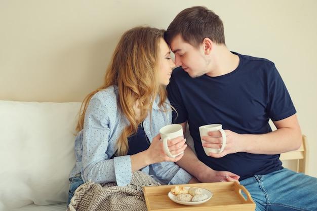 침대에서 커피를 마시는 젊은 부부