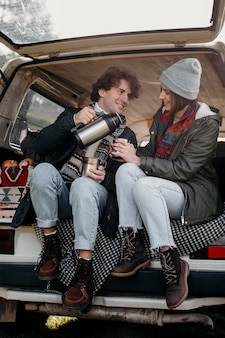 Young couple drinking coffee in a van