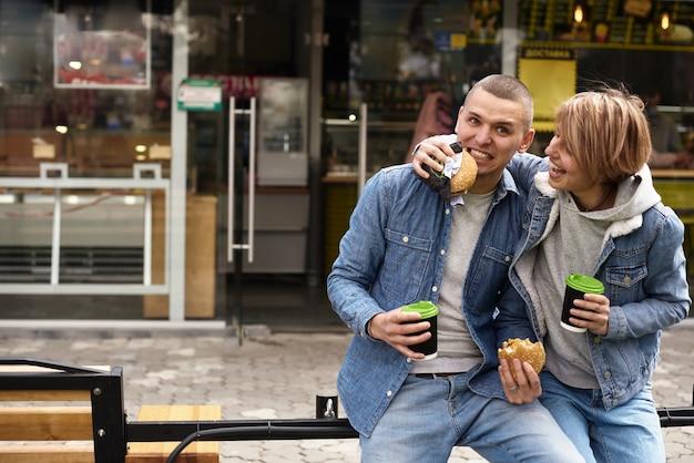 도시를 산책하면서 커피를 마시는 젊은 부부