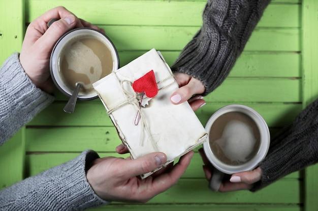 デートで木製のテーブルでホットコーヒーを飲む若いカップル