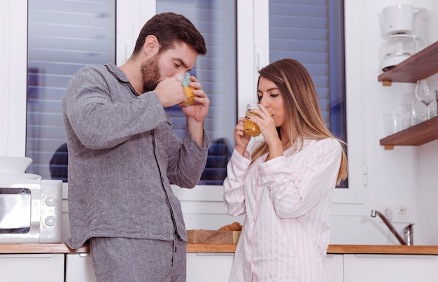 Young couple drinking orange juice in kitchen