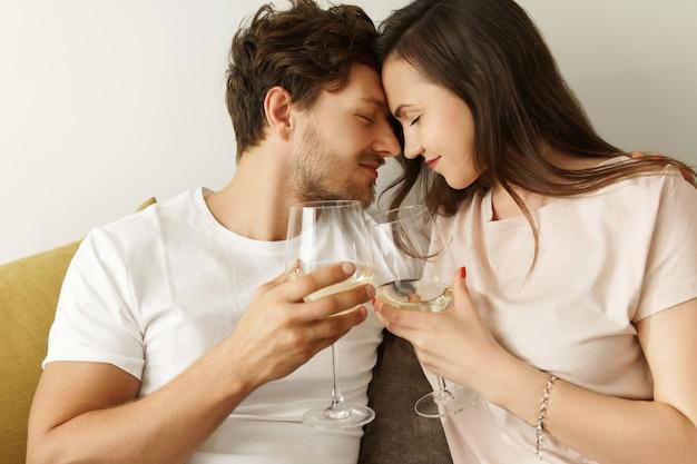 화이트 와인을 마시고 집에서 휴식을 취하는 젊은 부부