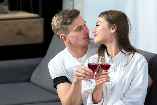 Young couple drinking wine on couch