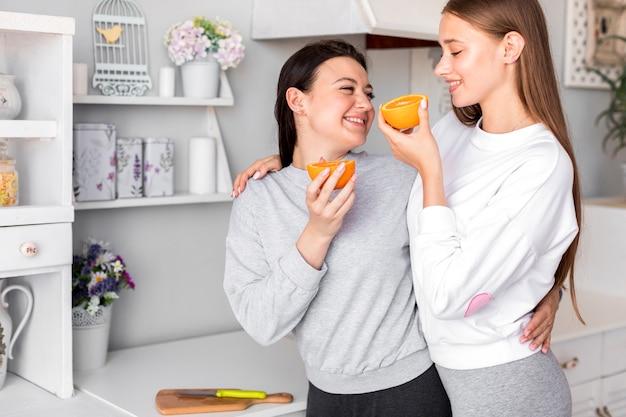 若いカップルが台所でオレンジを食べる