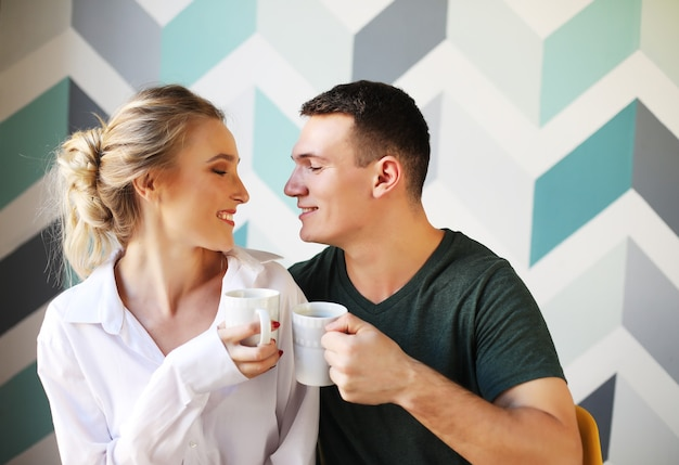 Young couple eating breakfast early in the morning in the kitchen and having a good time.