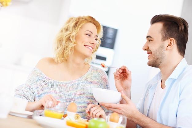 부엌에서 아침을 먹고 젊은 부부