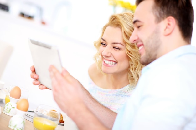 Young couple eating breakfast in the kitchen and using tablet