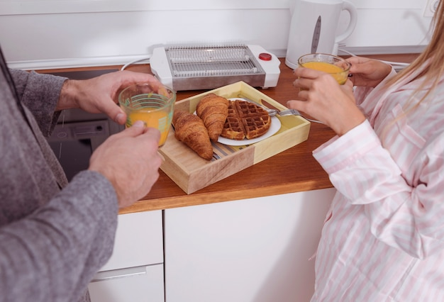 Young couple eating breakfast in kitchen