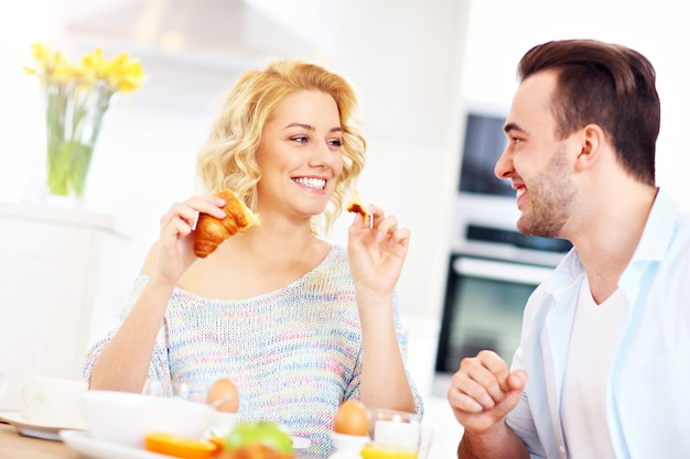 Young couple eating breakfast in the kitchen