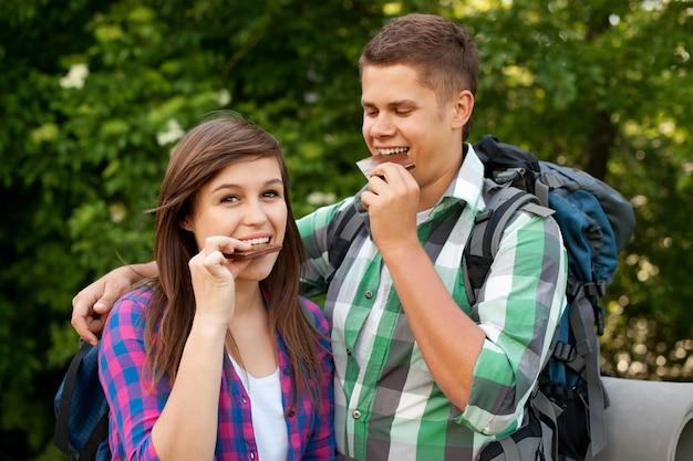 Giovani coppie che mangiano cioccolato nella foresta